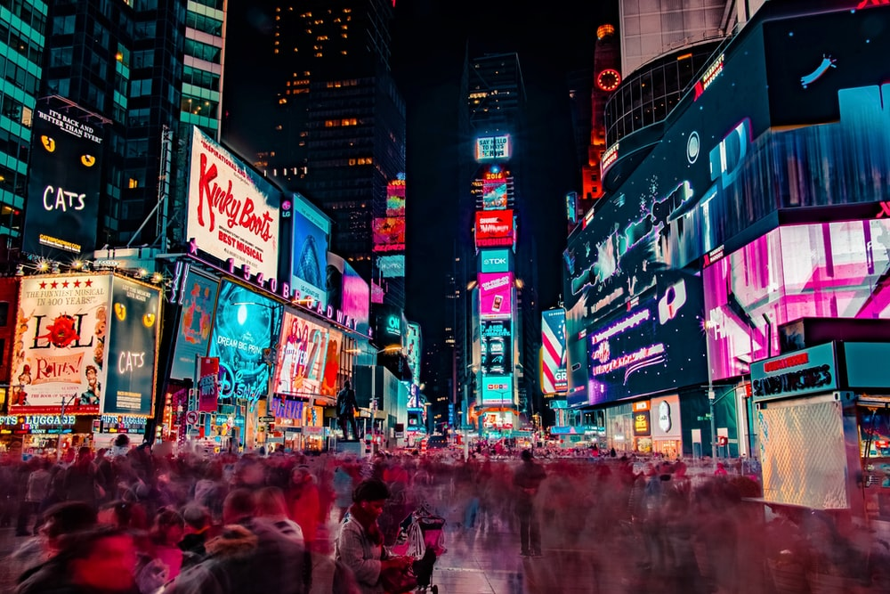 time-lapse photography of crowd of people on New York Time square during night time